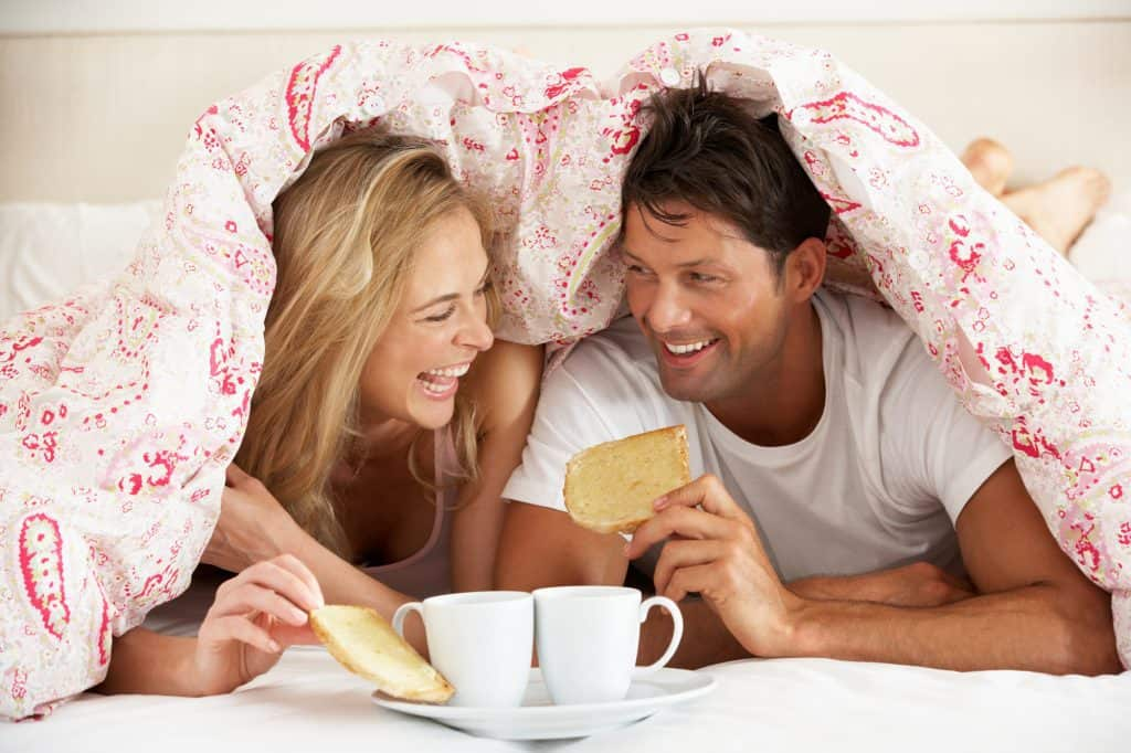 Couple Laughing And Having Coffee In Bed