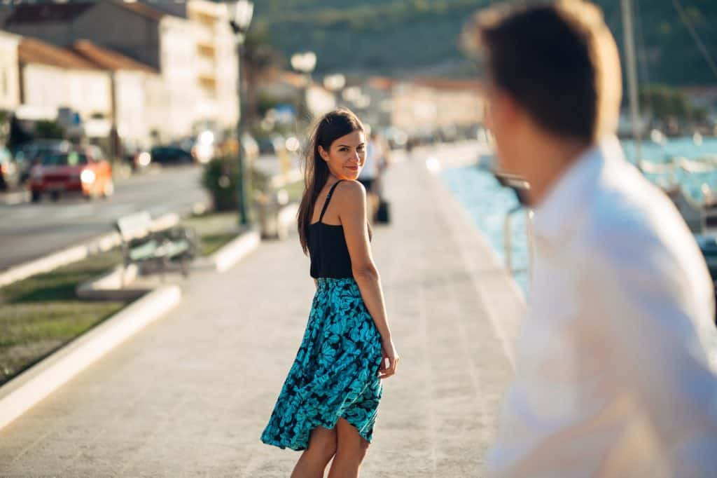 Couple Looking Back At Each Other While Walking Away