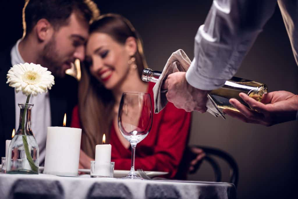 Couple On A Date Server Pouring Wine