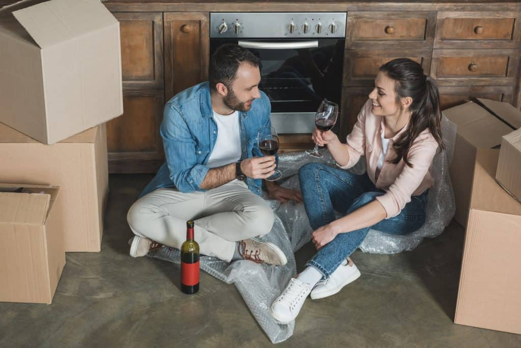 Friends Having Wine Sitting On The Floor With Boxes
