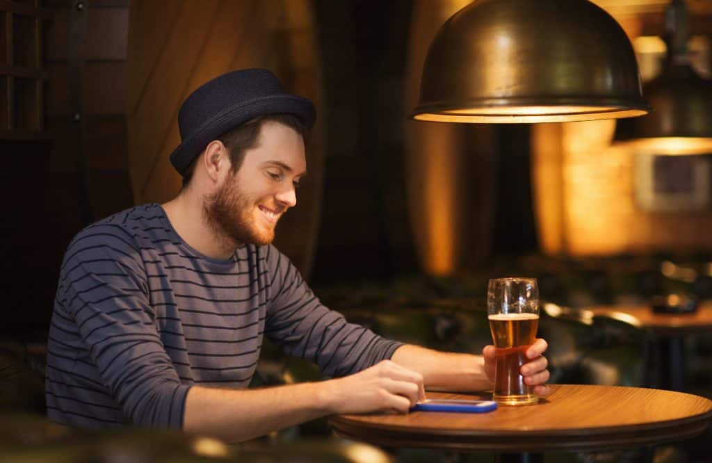Man At A Bar Smiling And Texting