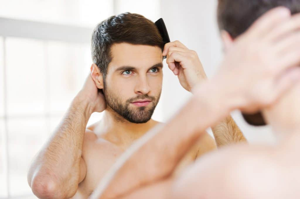 Man Fixing His Hair Infront Of A Mirror