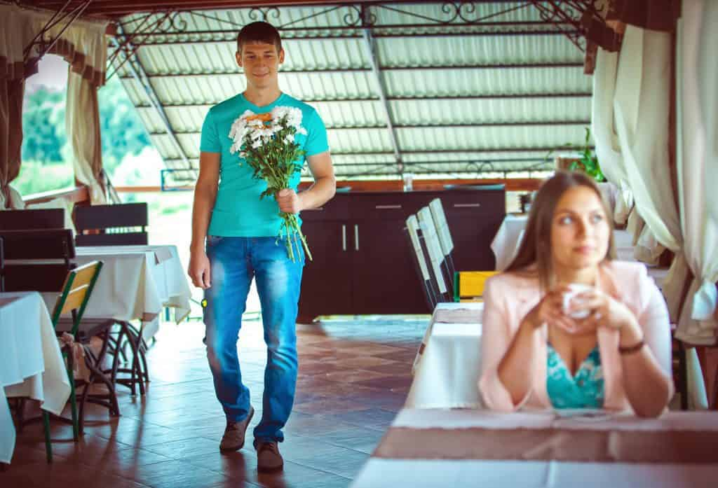 Man Holding A Bouquet Of Flowers Walking Towards Girlfriend