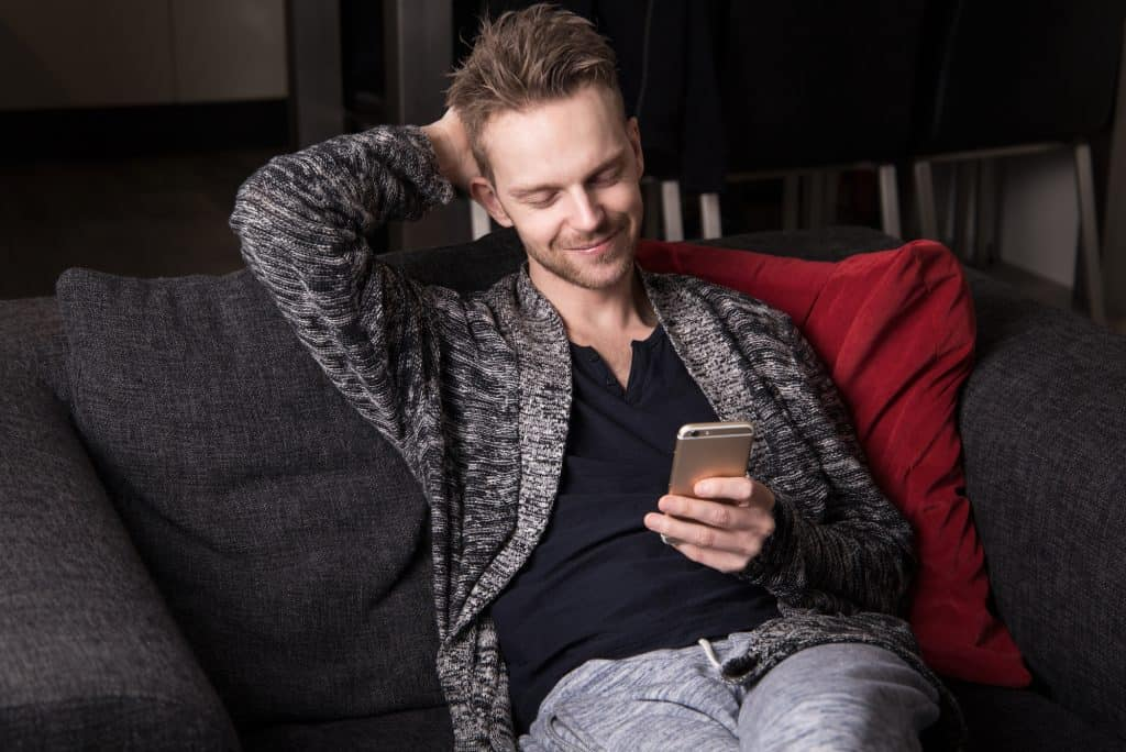 Man Smiling While Texting