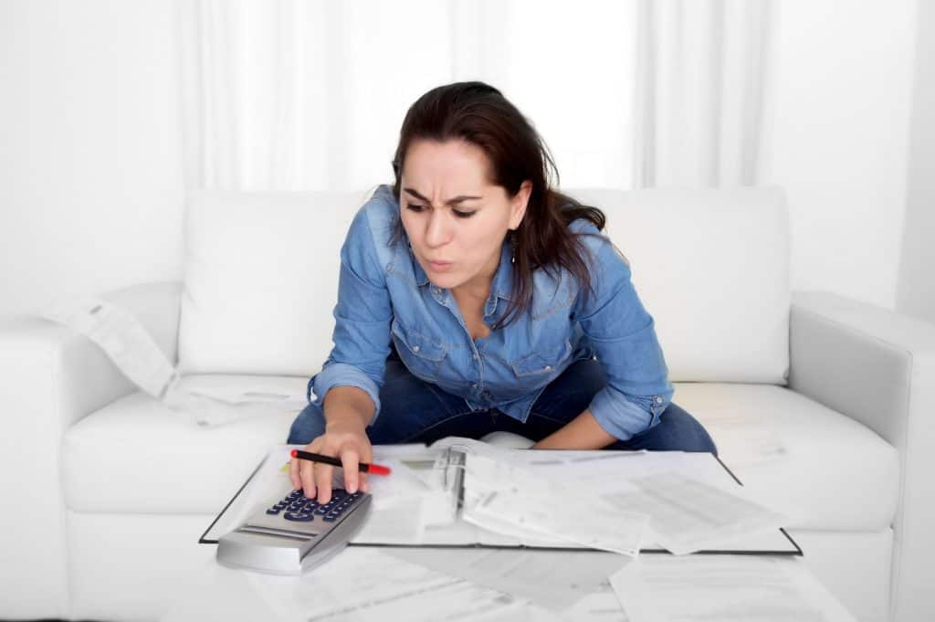 Woman Computing And Looking At Receipts