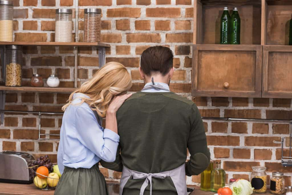Woman Leaning On A Man In The Kitchen