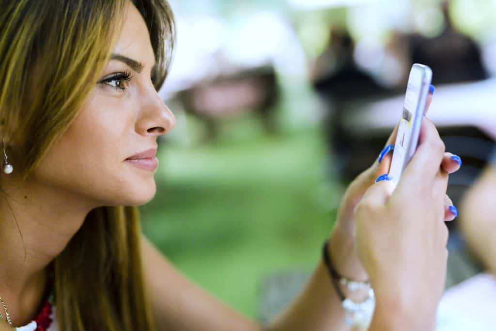 Woman Smiling Reading A Text Message