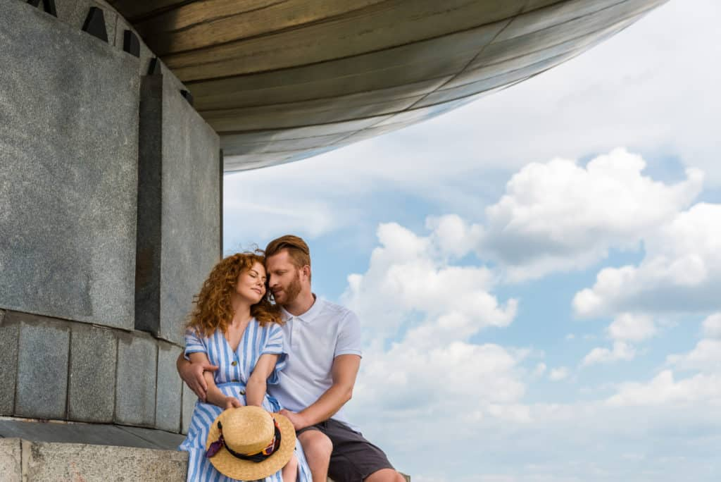 Blue Skies Couple Sitting On A Building