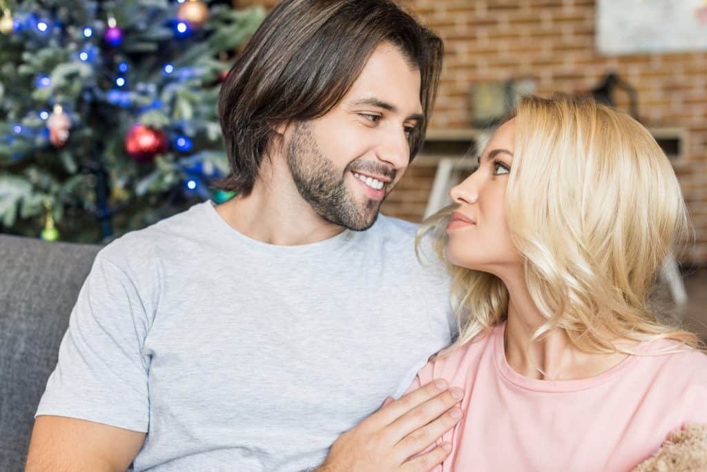 Couple At Home With A Christmas Tree