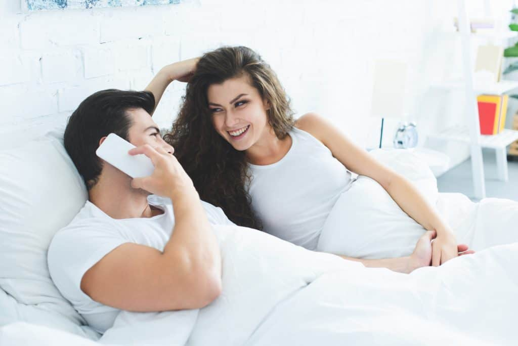 Couple In Bed Laughing Man On The Phone