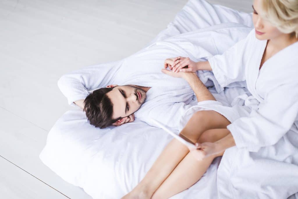 Couple In Bed Man Holding Wife's Hand