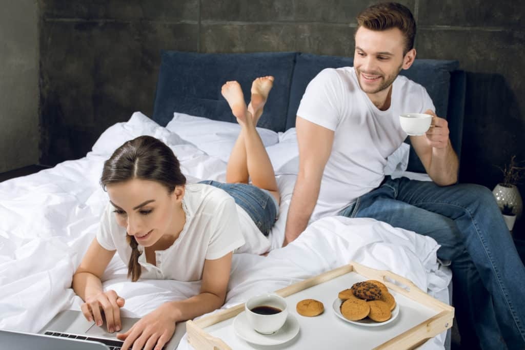 Couple In Bed Woman Using Laptop Man Having Coffee