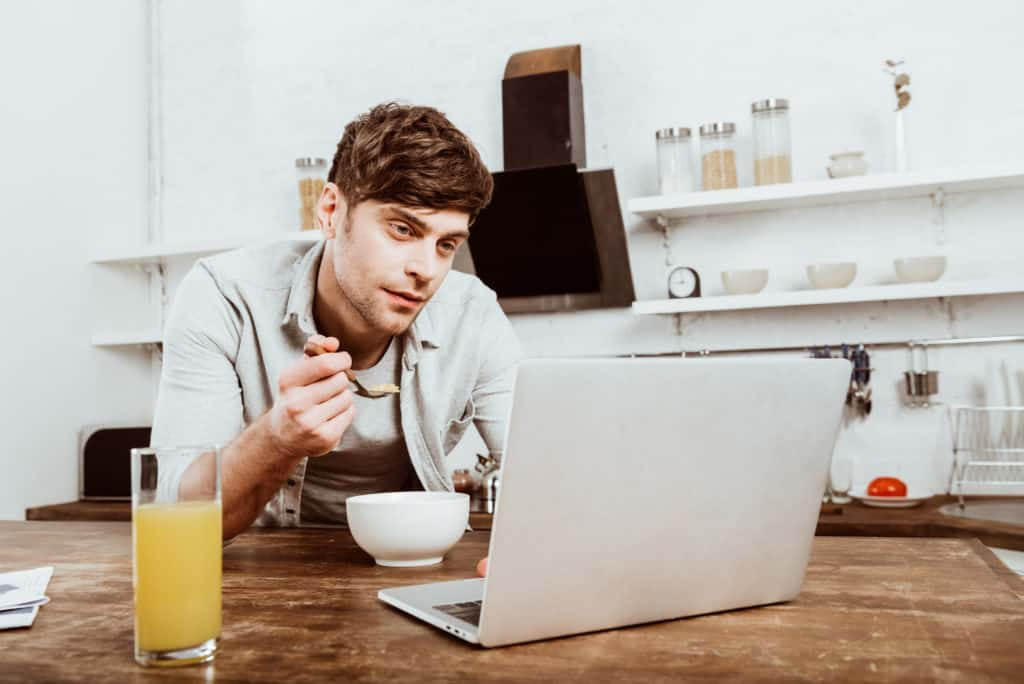 Man Eating Infront Of His Laptop