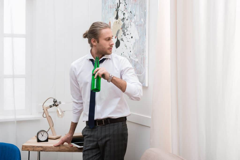 Man In Work Clothes Holding A Bottle