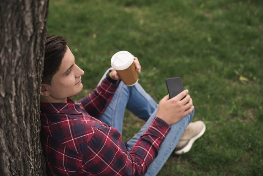Man Leaning On A Tree Holding A Coffee And His Phone