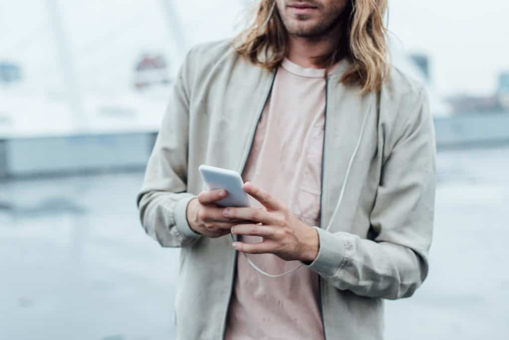 Man Wearing A Coat Texting