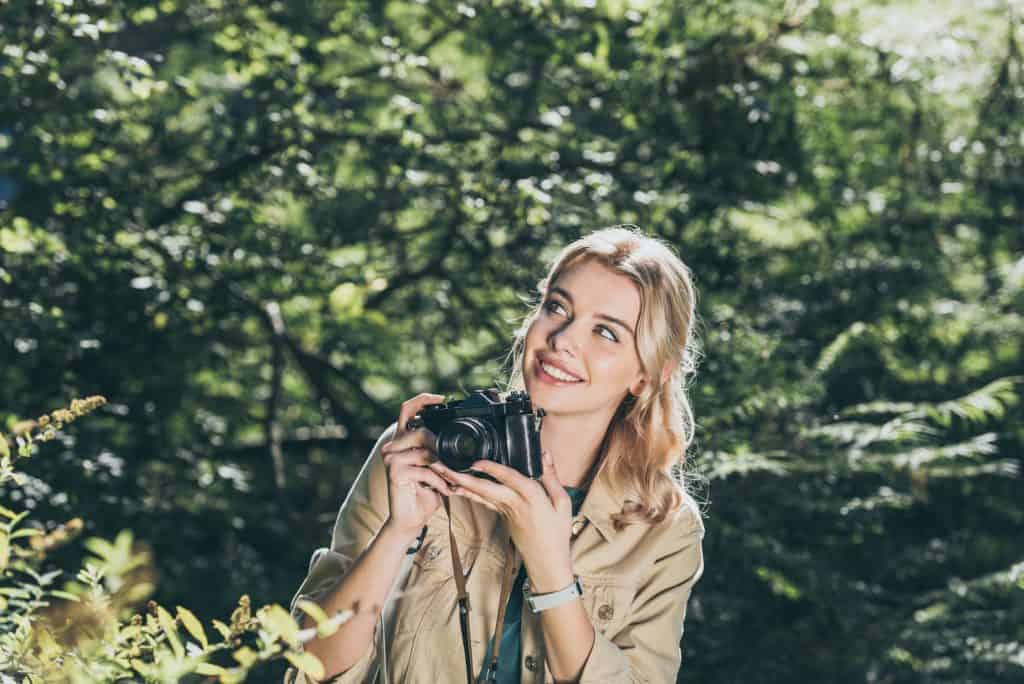 Woman Holding A Camera Outdoors