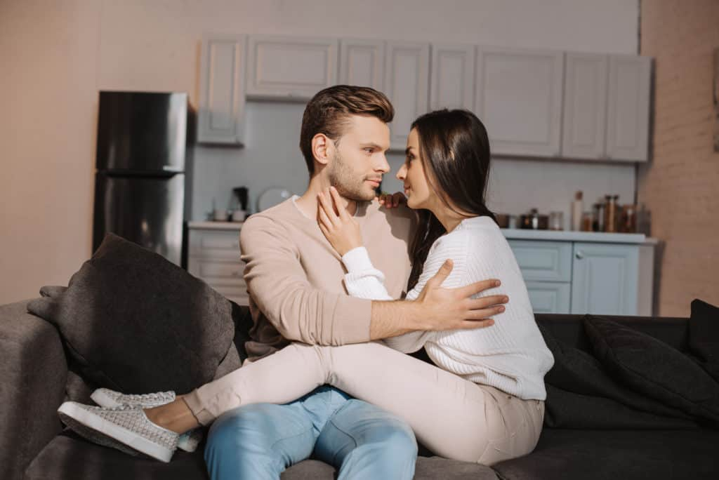 Woman On Boyfriends Lap Looking At Each Other