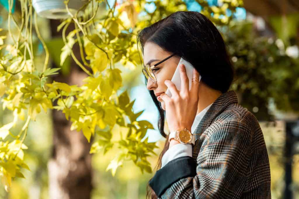 Woman On The Phone Beside A Plant