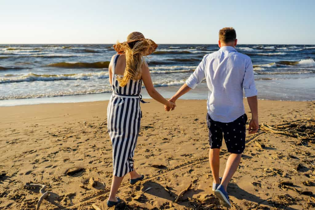 Couple Holding Hands Walking On The Shore