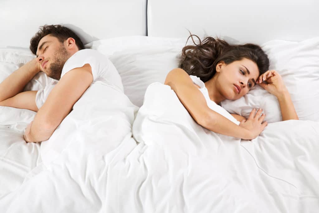 Couple In Bed Not Talking To Each Other