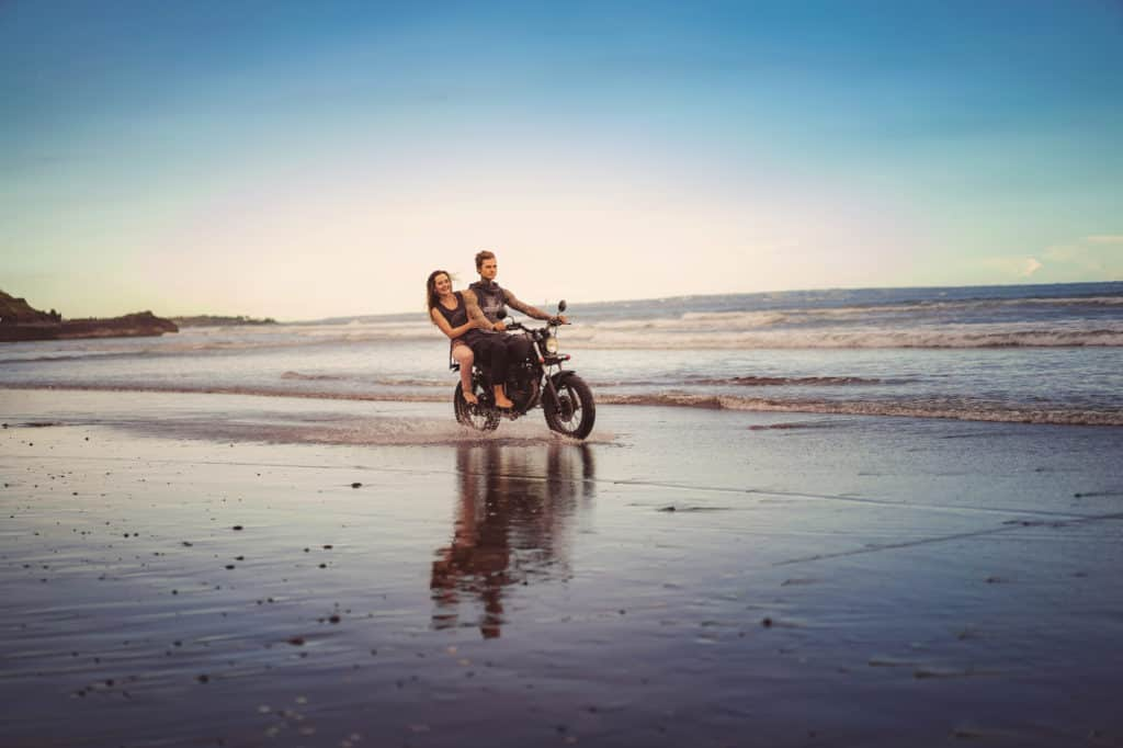 Couple On A Motorbike By The Beach