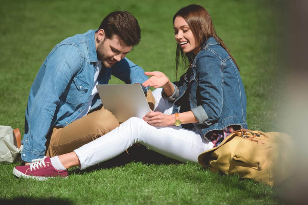 Couple Sitting On Grass With A Laptop