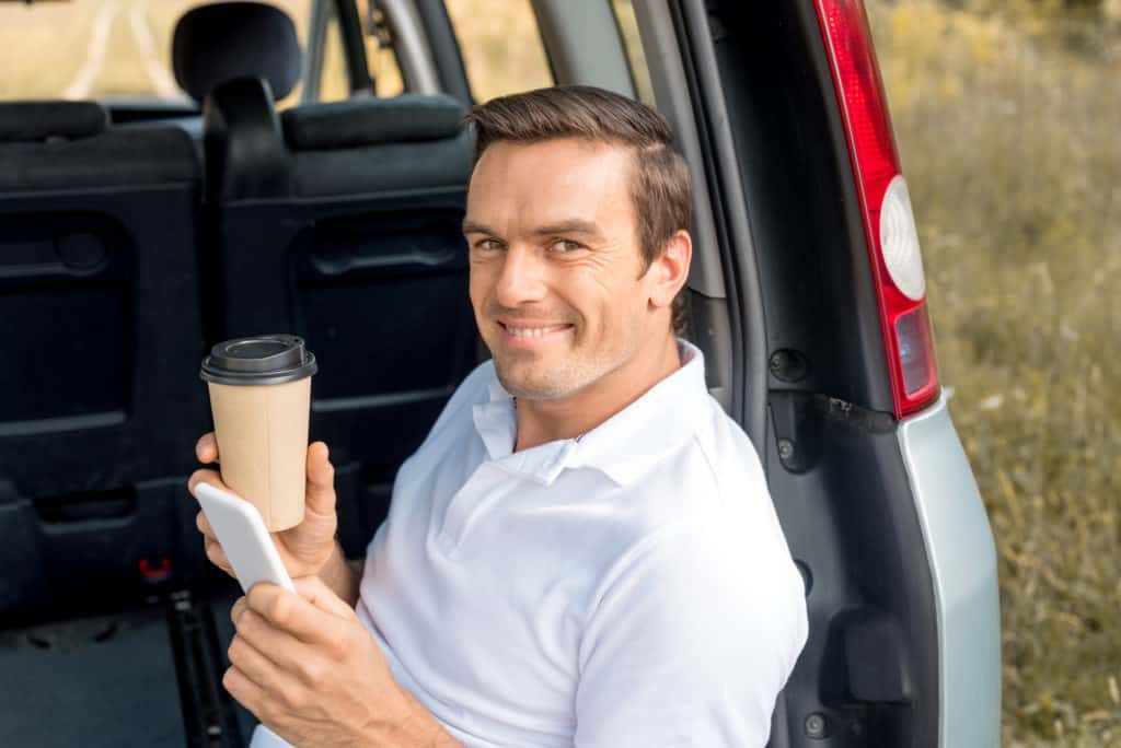 Man Sitting On A Car With Coffee And His Phone