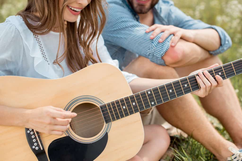 Woman Playing The Guitar With Man Beside Her