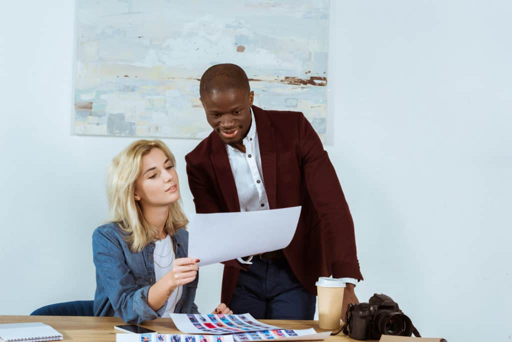 Woman Showing Paperwork To Male Colleague